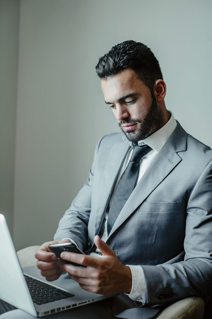 Businessman using laptop and cell phone in armchair