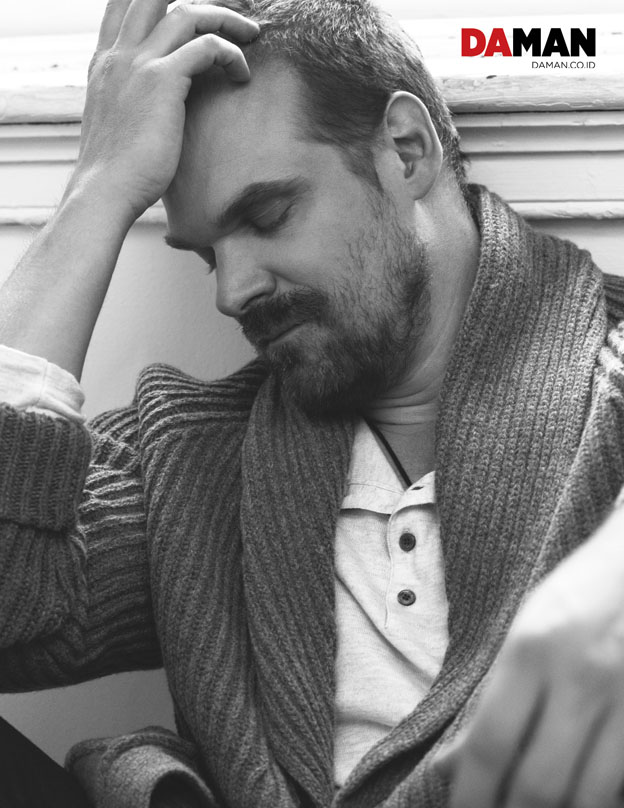 David Harbour of Netflix's Stranger Things in Shirt and cardigan by Vince, denim trousers by 7 for All Mankind
