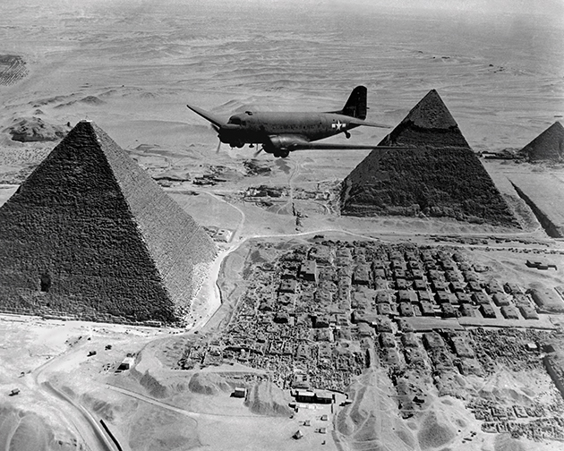 A WWII-era DC-3 flying above the pyramids at Giza